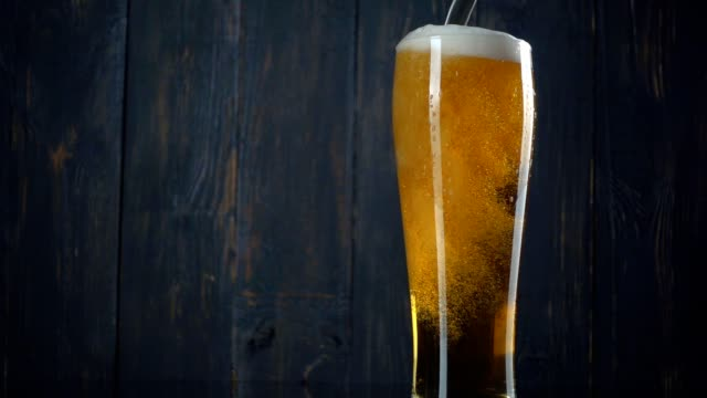 Pouring beer into glass over dark wooden background. Slow motion video
