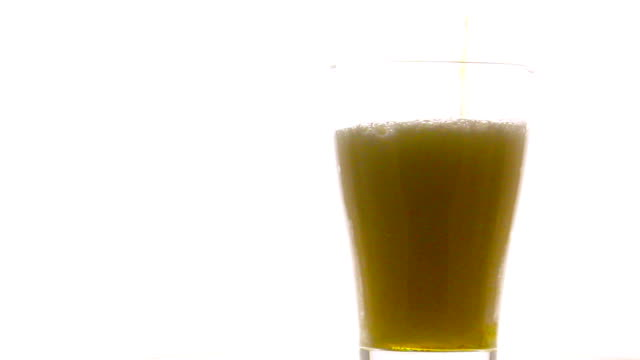 Pouring beer into rotate glass on white background video