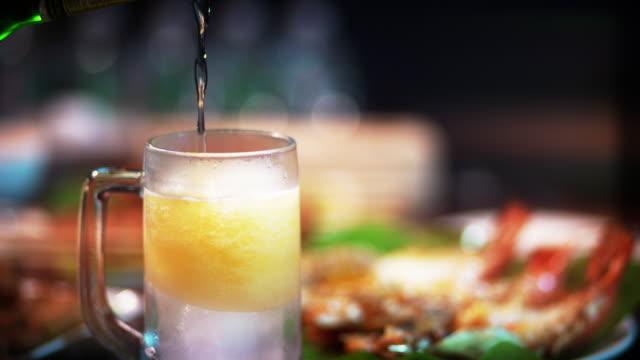 versare birra nel bicchiere sul tavolo del ristorante - fragilità video stock e b–roll