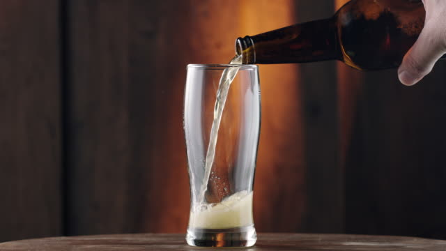 Pouring beer Close-up, pouring beer from beer bottle into glass pouring stock videos & royalty-free footage