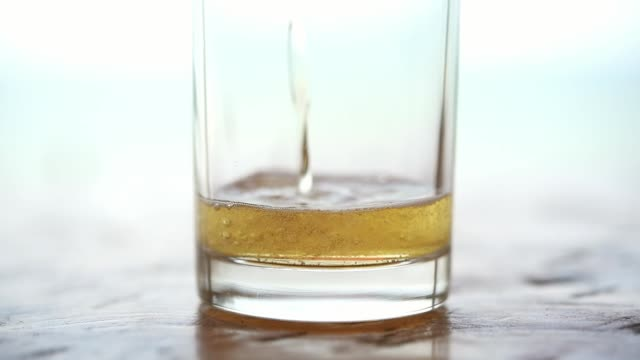 pouring beer water in to glass with ice and froth - tavolo legno video stock e b–roll