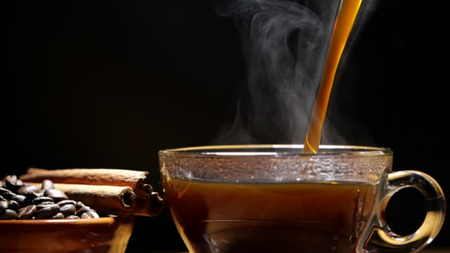 Pouring black coffee in a cup with steam in slow motion on black background