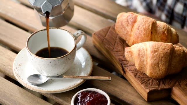 pouring black coffee into cup - pausa caffè video stock e b–roll