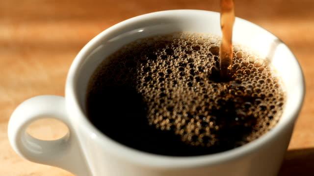 vídeos y material grabado en eventos de stock de verter el café a una taza con vapor natural y burbujas en él - café negro