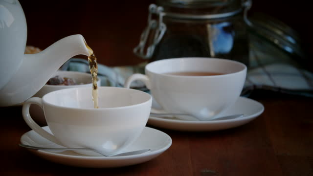pouring black tea into cup - tea cup stock videos & royalty-free footage