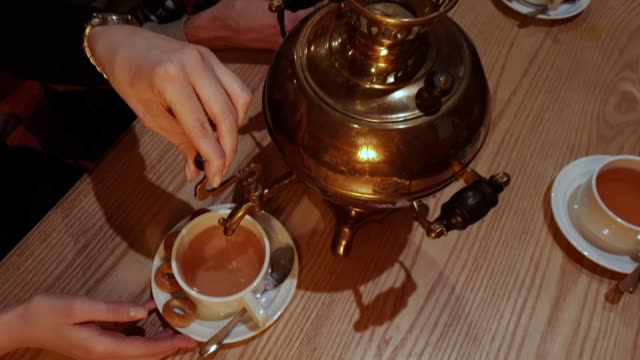 Pouring boiling brewed tea from Russian kettle Samovar, traditional Russian samovar with bagels, people pour tea from an old copper samovar Pouring boiling brewed tea from Russian kettle Samovar, traditional Russian samovar with bagels, people pour tea from an old copper samovar mug stock videos & royalty-free footage