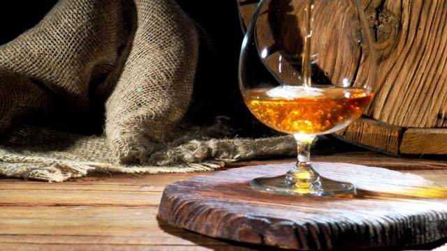 vídeos de stock e filmes b-roll de pouring brandy next to the barrel - barrica