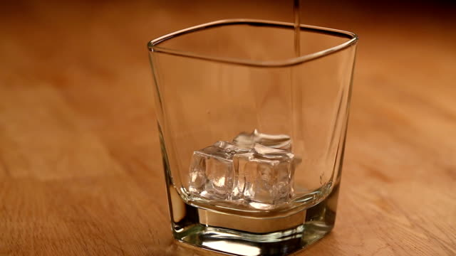 pouring brandy with ice cubes video
