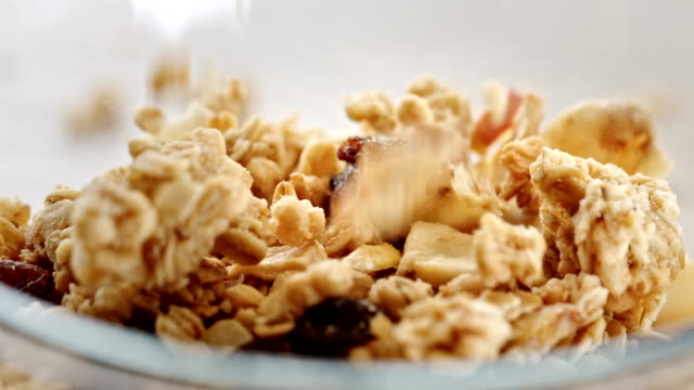 vídeos de stock e filmes b-roll de pouring breakfast cereals into a bowl - granola