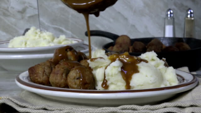 Pouring brown gravy over potatoes