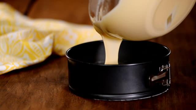 vídeos de stock e filmes b-roll de pouring cake mixture into baking tin. - utensílio