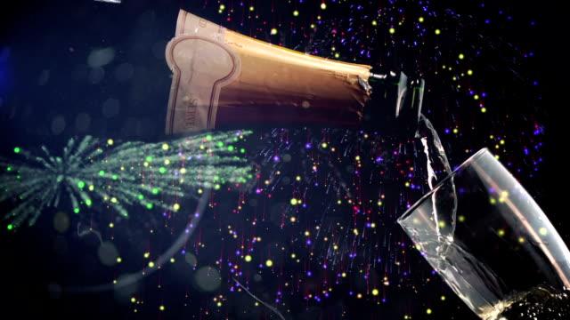 El vertido en copa de champán con fuegos artificiales en el fondo - vídeo
