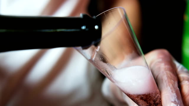 Pouring champagne into glass at party, close up video