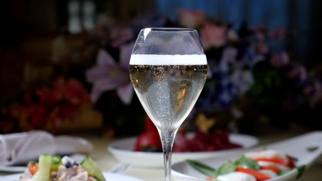 Pouring champagne into glass. Close up. Slow motion.