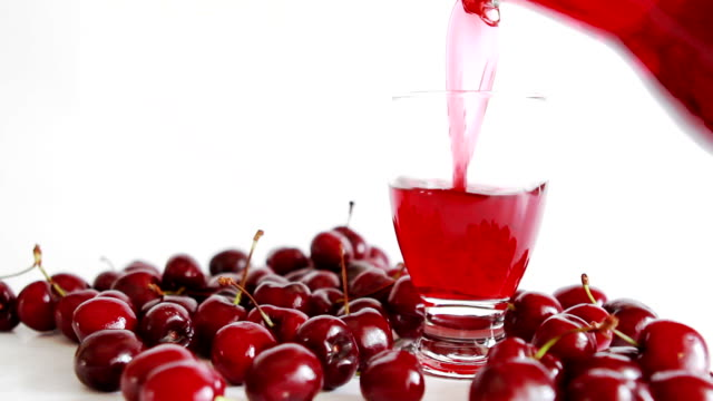 pouring cherry juice into glass. video
