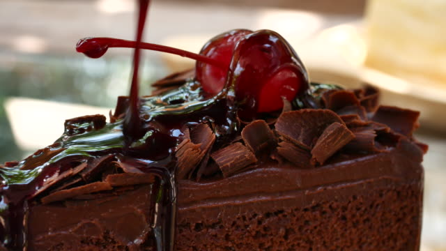 Pouring chocolate dressing over slice of cake video