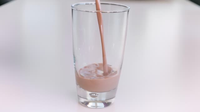 pouring chocolate milk in drinking glass