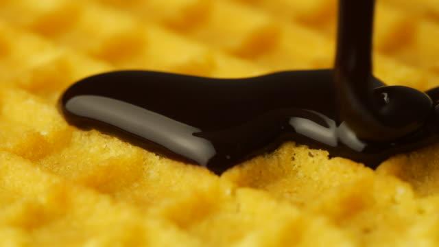 vídeos y material grabado en eventos de stock de pouring chocolate en un gofre crujiente a cámara lenta, primer plano - galleta dulces