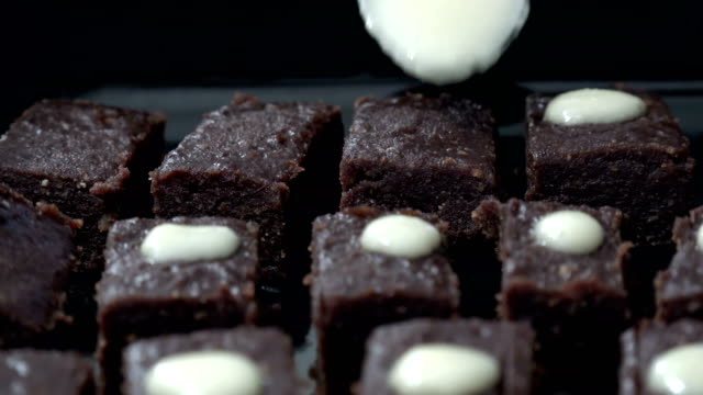Pouring chocolate on cube brownies cakes, home preparation video