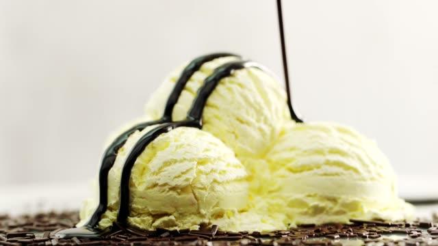 Pouring chocolate sauce over vanilla ice cream