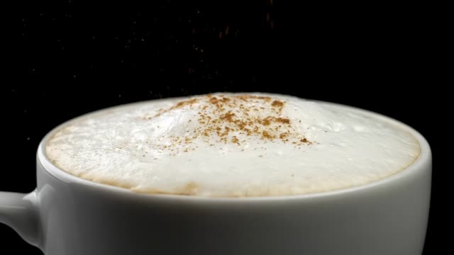 Pouring cinnamon powder into cappuccino coffee cup . Black background. Close-up shot. Slow motion