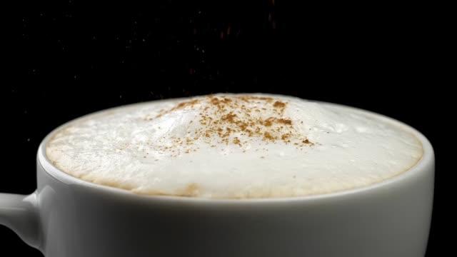 zimtpulver in cappuccino kaffeetasse gießen. schwarzer hintergrund. nahaufnahme. die zeitlupe - cappuccino stock-videos und b-roll-filmmaterial