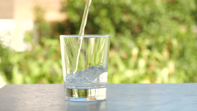 Pouring clean water into the glass in the Garden Outdoor