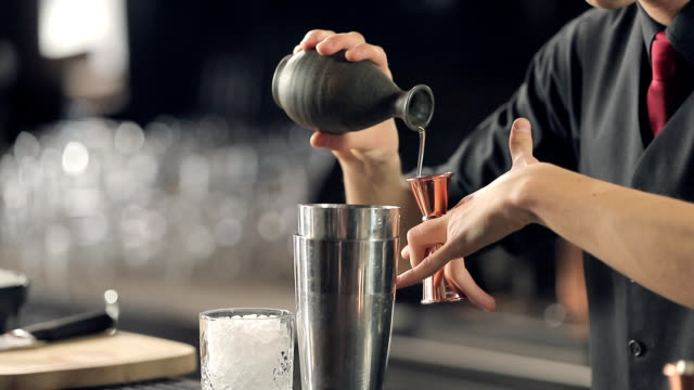 Pouring cocktail ingredient into the jigger from jug