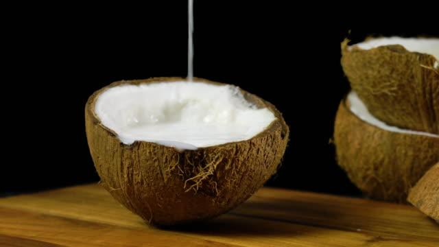 vídeos de stock e filmes b-roll de pouring coconut milk into a half shell against a black background. - oleo palma
