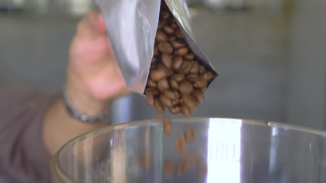 SLOMO pouring coffee beans from a bag SLOMO pouring coffee beans from a bag grind stock videos & royalty-free footage