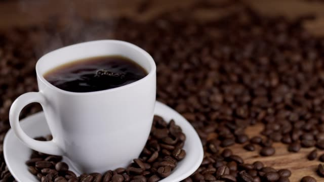 pouring coffee from coffee pot in white cup surrounded by coffee beans in 4k uhd - pausa caffè video stock e b–roll