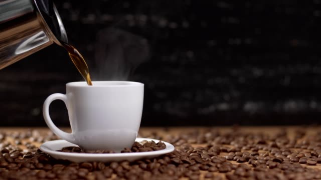 pouring coffee in white cup surrounded by coffee beans on dark background. 4k - pieno video stock e b–roll