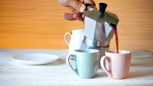 pouring coffee into a cups at the kitchen