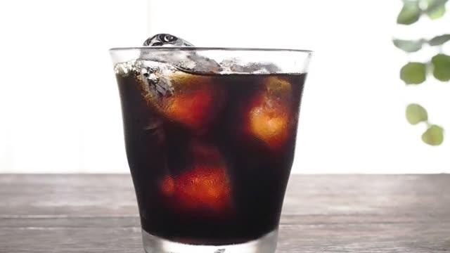 vídeos de stock e filmes b-roll de pouring coffee into a glass with ice. - café gelado