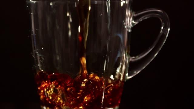 vídeos y material grabado en eventos de stock de verter el café en la taza de café - cámara lenta - café negro