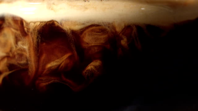 Pouring coffee. Mixing layers Frothy coffee drink poured into transparent glass. Layers mixing together. Abstract patterns coffee stock videos & royalty-free footage