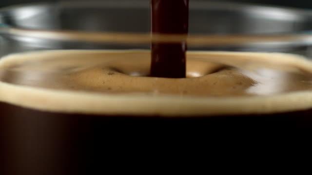 vídeos de stock e filmes b-roll de pouring coffee. mixing layers - bebida com espuma