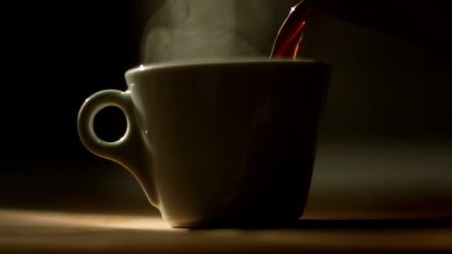 Pouring coffee to a cup with natural steam on it video