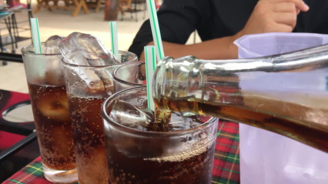 pouring coke/cola/soda into a glass on a table - soda pop stock videos & royalty-free footage