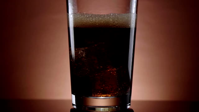 Pouring cola in a glass with ice cubes - refreshing soda video