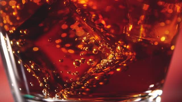versando cola in un bicchiere su sfondo rosso - ritemprarsi video stock e b–roll