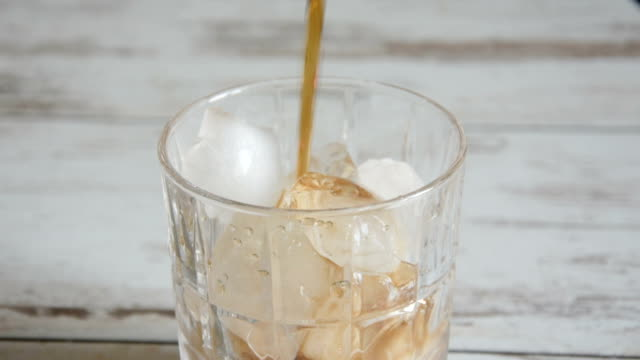 Pouring cola into a glass with ice cubes from a height.