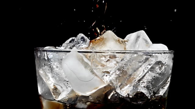 Gießen Limonade in Glas Cola mit Eis mit Akzenten in Zeitlupe auf dem schwarzen Hintergrund – Video