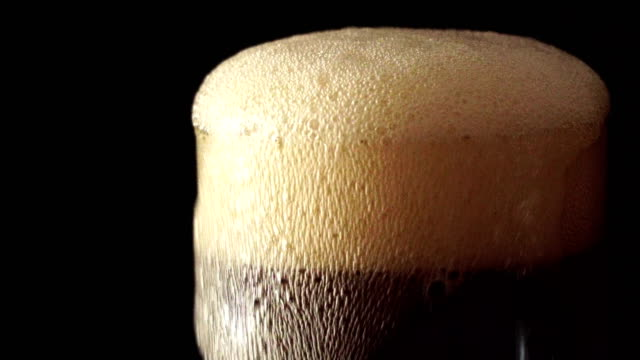 Pouring cola soda into glass of ice with splashes on a black background video