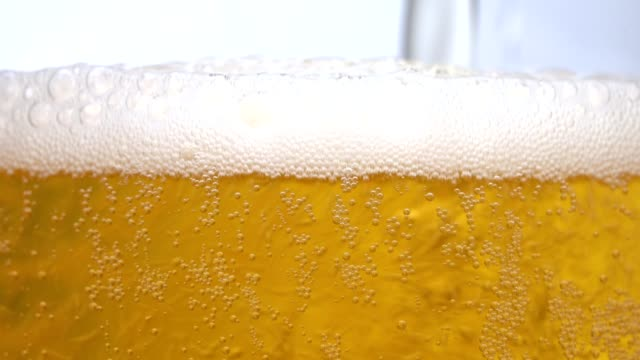 Pouring Cold Beer into a glass with water drops