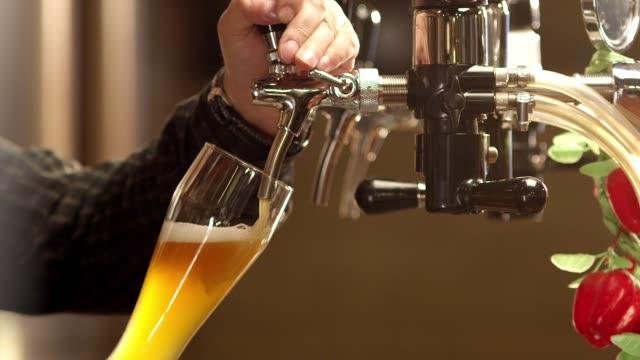 Kaltes Bier in Sglas gießen. Bartender gießt Craft-Bier in der Bar. Die Hand eines Braumeisters gießen aus dem Fass einen leichten Bierschaum. Stout, Licht, ungefiltertes Bier, trinkfertig. Zeitlupe. – Video