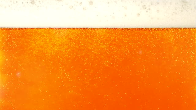 Pouring cold beer into glass. Closeup. Slow motion video