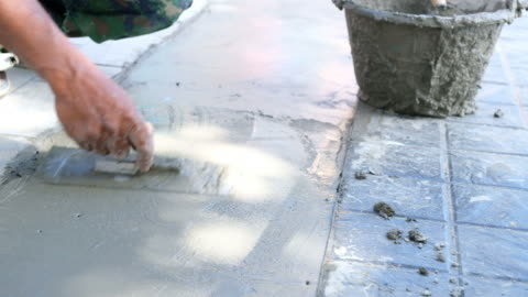pouring concrete worker utilizza una pala per livellare e lisciare il calcestruzzo bagnato sul pavimento nel video stock 4k del cantiere - calcestruzzo video stock e b–roll