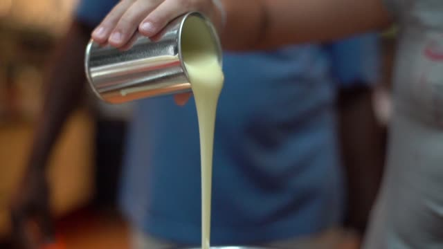vídeos de stock, filmes e b-roll de derramar o leite condensado para preparar o brigadeiro brasileiro - brigadeiro