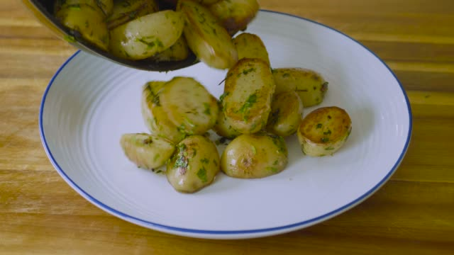 pouring cooked new potatoes on plate
